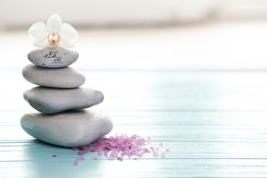 Spa stones, sea salt and flower on table against blurred background. Space for text