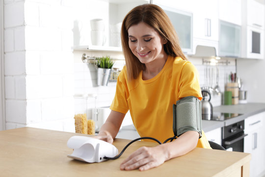 Woman checking blood pressure with sphygmomanometer at table indoors. Cardiology concept
