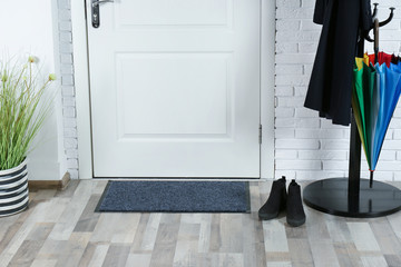 Hallway interior with mat and clothes stand near door