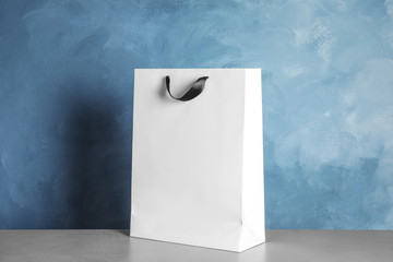 Paper shopping bag on table against color background. Mock up for design