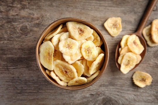 Bowl and spoon with sweet banana slices on wooden table, top view. Dried fruit as healthy snack