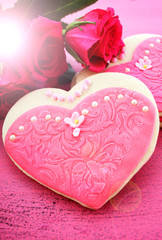 International Women's Day heart shape cookies decorated as pink ladies dresses with bouquet of pink roses on vintage pink wood with lens flare