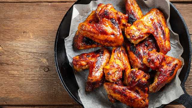 Baked chicken wings in barbecue sauce in a cast iron pan on an old wooden rustic table. Top view with copy space
