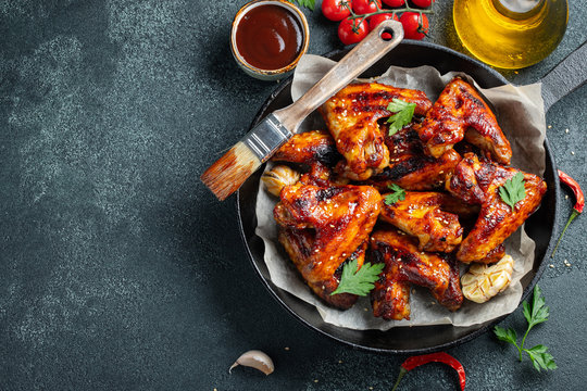 Baked chicken wings in barbecue sauce with sesame seeds and parsley in a cast iron pan on a dark concrete table. Top view with copy space