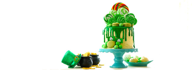 St Patrick's Day party table with lollipop candyland drip cake on white background.
