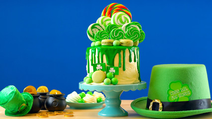 St Patrick's Day party table with lollipop candyland drip cake on blue chroma key background.