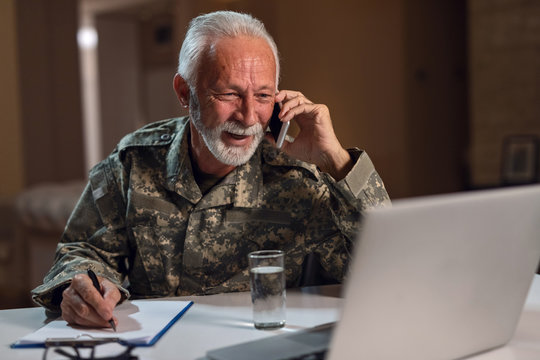 Happy mature army soldier working in the office and talking on the phone.