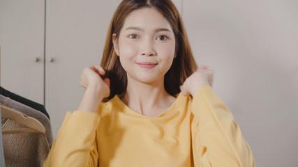 Beautiful attractive young Asian woman choosing her fashion outfit clothes in closet at home or store. Girl think what to wear sweater. Home wardrobe or clothing shop changing room.