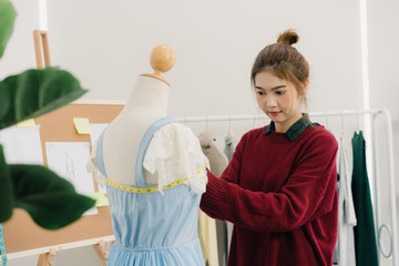 Professional beautiful Asian female fashion designer working measuring dress on a mannequin clothing design at the studio. Lifestyle women working concept.