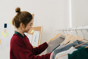 Asian female fashion designer working, checking and choosing clothes design on clothes rack while working in the fashion studio. Lifestyle beautiful professional designer women working concept.