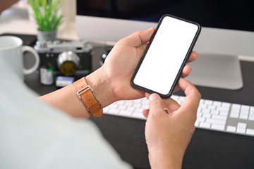 Mobile phone in man hands on workspace
