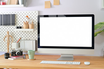 Workspace with computer with blank white screen