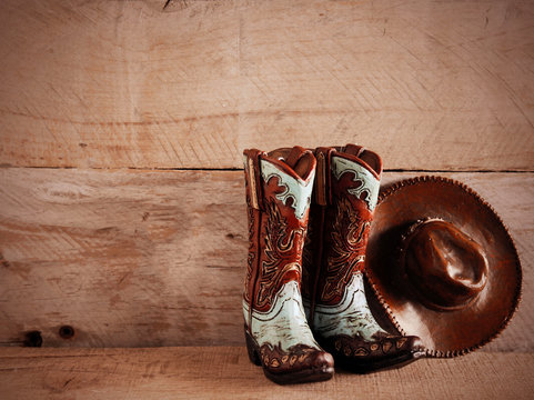 pair of cowboy boots and hat on a wood background in sepia tone with writing space