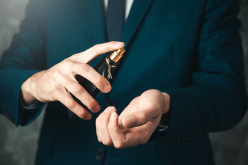 man hand perfume on dark background