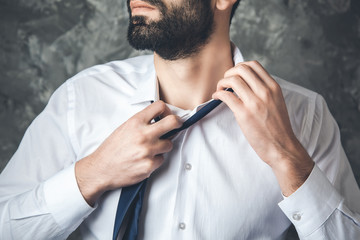 business man remove tie on dark background