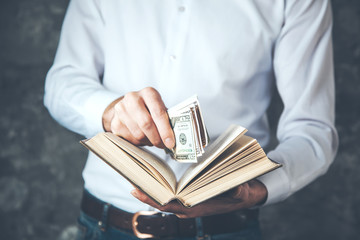 man hand money with book on dark background