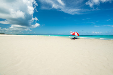 Amazing beach of Varadero during a sunny day, fine white sand and turquoise and green Caribbean sea,on the right one red parasol,Cuba.concept  photo,copy space.