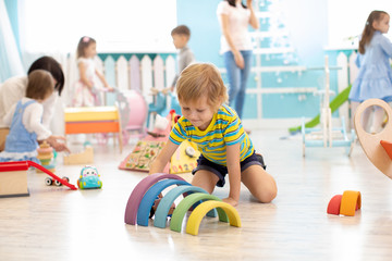 Kids playing on floor with educational toys. Toys for preschool and kindergarten. Children in nursery or daycare
