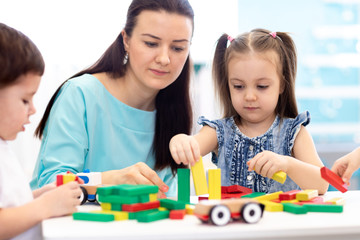 Little children building block toys with carer at home or daycare. Kids playing with color blocks. Educational toys for preschool and kindergarten pupils.