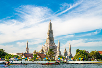 Wall Mural - Temple of dawn Wat Arun with boat blue sky sunny day