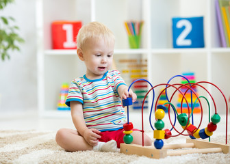 Preschooler child boy playing with developmental toy. Kid plays with toy beads at kindergarten or daycare center. Toddler baby in nursery room.