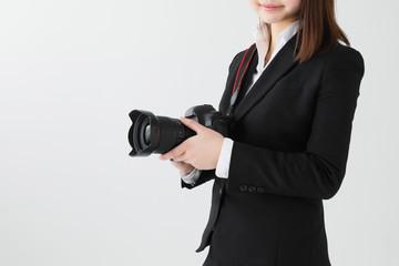白背景でスーツを着てカメラを持つ女性プロカメラマン