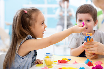 Children girl and boy playing with plasticine in kids daycare center