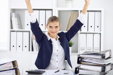 Modern business woman or confident female accountant in office with arms raised represents success at work. Student girl during exam preparing. Audit, tax service or education concept