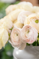 Persian buttercup. Bunch pale pink and pastel yellow ranunculus flowers in Glass vase. Vertical Wallpaper