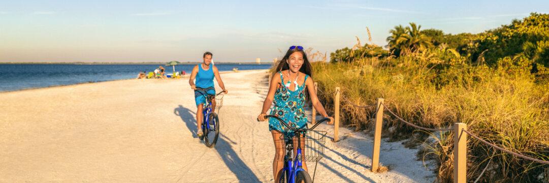 People having fun summer lifestyle riding bikes biking on beach in Florida sunset background. Panoramic banner. Asian girl laughing on recreatinal bike, man bicycling.