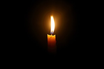Light for life - Yellow candle light against black background