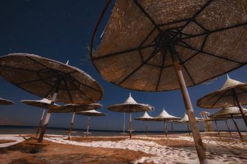 straw umbrellas on sandy sea (ocean) beach on exotic resort. summer landscape