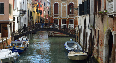 Small Venice Canal with Boats Bridge and People.