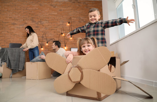 Children playing with cardboard box on moving day