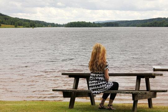 A woman on a bench by a lake