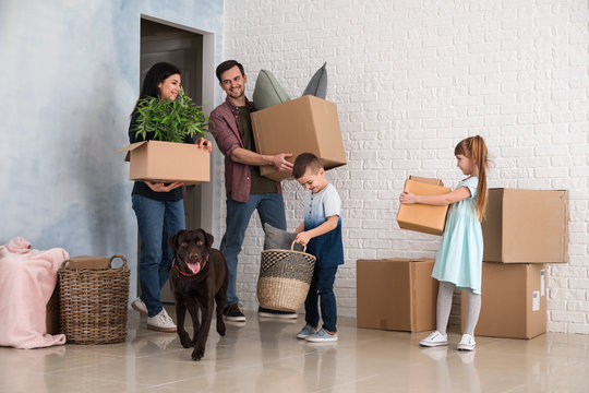 Family with cardboard boxes after moving into new house