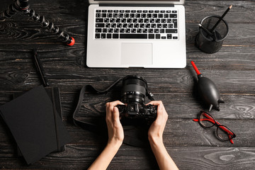 Female photographer with camera and laptop at workplace, top view