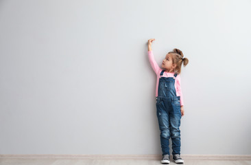 Portrait of cute little girl near light wall