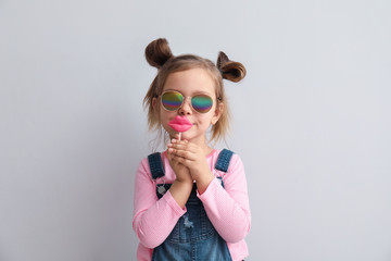 Portrait of stylish little girl with lollipop on light background Wall mural