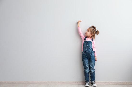 Portrait of cute little girl near light wall