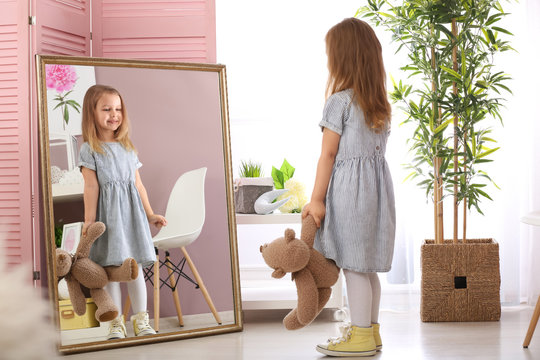 Cute little girl with teddy bear looking in mirror at home