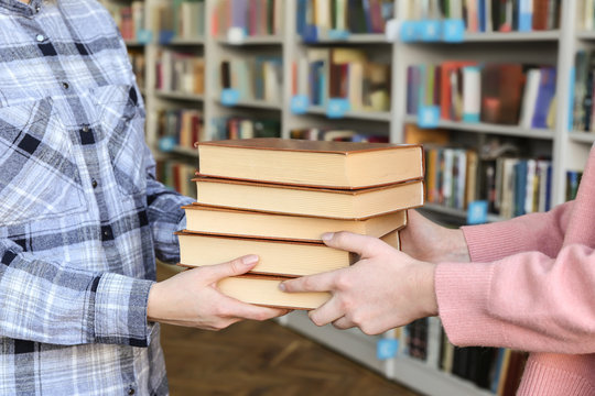 Young woman receiving books from librarian