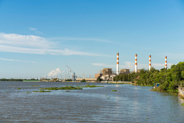 Natural gas electric power plant with smokestack at riverside in chonburi thailand and beautiful sky