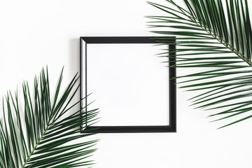 Summer composition. Tropical palm leaves, black photo frame on white background. Summer, nature concept. Flat lay, top view, copy space