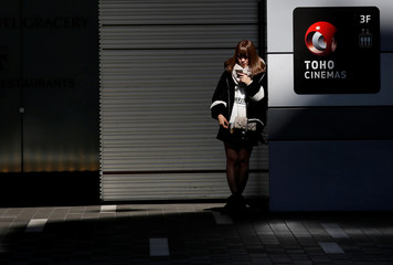 A woman stands next to the logo of Toho Cinemas at its multiplex chain in Tokyo
