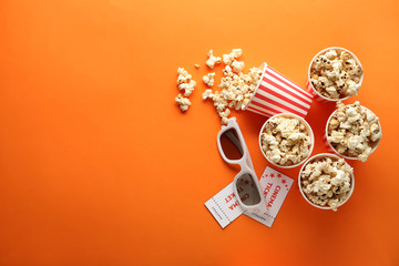 Paper cups of tasty popcorn, tickets and cinema glasses on color background
