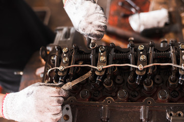 An old tractor repairman is working with a car engine in a garage, repairing the actual close-up pictures.