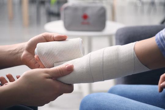 Woman applying bandage onto female arm, closeup