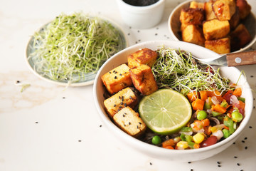 Bowl with tasty fried tofu cheese and vegetables on table
