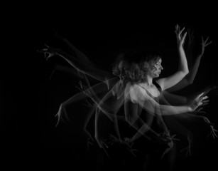 Stroboscopic photo of beautiful moving young woman on dark background